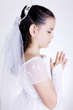 Pray. Girl praying with her hands clasped and white dress. First Communion Stock Photo
