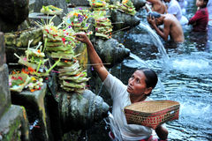 Pray. Persons pray and bath themselves in the sacred waters of the fountains in Tirta Empul, Bali, Indonesia Royalty Free Stock Images