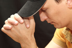 Pray. A man in a cap praying to God Stock Photo