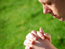 Pray. Cropped image of a young man praying on a green grass background Stock Image