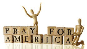 Pray for America. Rustic alphabet blocks arranged to say, Pray for America.  Two artist's manniquins are nearby praying -- one standing with upraised head and Stock Images