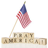 Pray America!. Rustic wooden alphabet blocks arranged to say Pray America!.  The stars and stripes fly overhead.  On a white background Royalty Free Stock Photos