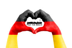 Pray for berlin, germany, city silhouette inside man hands in the form of heart with the flag of germany on the white background, Stock Images