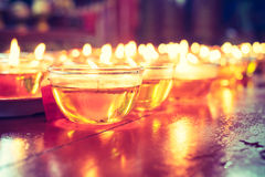 Pray candle glass on wood table in chinese temple.  Royalty Free Stock Photo