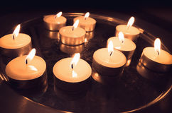 Pray candles burn on a metal stand. In dark church square Royalty Free Stock Images