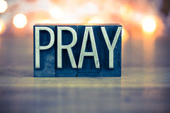 Pray Concept Metal Letterpress Type. The word PRAY written in vintage metal letterpress type on a soft backlit background Stock Image