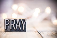 Pray Concept Vintage Letterpress Type Theme. The word PRAY written in vintage metal letterpress type on a bokeh light and wooden background Stock Photography