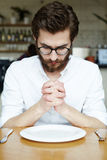 Pray before eating. Young man praying over empty plate at lunch break Stock Photography
