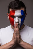 Pray France football fan in game  of France national  team with close eyes. Royalty Free Stock Photo