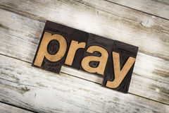 Pray Letterpress Word on Wooden Background. The word & x22;pray& x22; written in wooden letterpress type on a white washed old wooden boards background Royalty Free Stock Photography