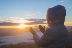 Pray in the Morning , Woman praying with hands together on the morning sunrise background royalty free stock photo