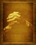 Pray old hands. Old praying hands on grunge, worn paper Royalty Free Stock Photos