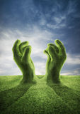 Pray for rain. 3D render of pleading grass covered hands rising from ground toward sky Stock Photos
