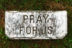 Pray for Us. A stone reading pray for us sitting in an old church cemetery Royalty Free Stock Photos