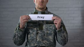 Pray word written on sign in hands of male soldier, serviceman asking for peace stock video