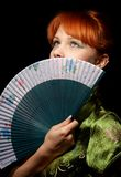 Prayer. Pretty redhead with green fan Royalty Free Stock Photography