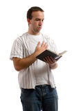 Prayer. A young man holding an old bible is saying a prayer, isolated against a white background Royalty Free Stock Images