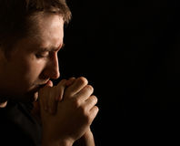 Prayer. Young man on black background stock images