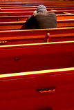 Prayer. View of a guy praying in a church royalty free stock photo