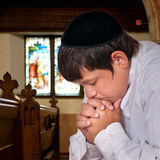 Jewish Boy Praying. Jewish boy prays alone in prayer house stock images