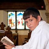 Prayer. Jewish boy looks towards the camera while praying at prayer house royalty free stock image
