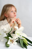 Prayer. Little blond girl counting the rosary Royalty Free Stock Photography