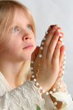 Prayer. Little blond girl counting the rosary Stock Images