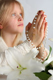 Prayer. Little blond girl counting the rosary Stock Photography
