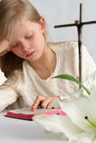 Prayer. Little girl reading holy bible  and easter lilies lying on the table Royalty Free Stock Photo