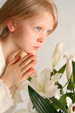 Prayer. Little girl praying on the easter lilies background Royalty Free Stock Image