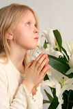 Prayer. Little girl praying on the easter lilies background Royalty Free Stock Photo