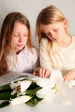 Prayer. Two sister reading holy bible together and easter lilies lying on the table Royalty Free Stock Photo