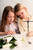 Prayer. Two sister reading holy bible together and easter lilies lying on the table Royalty Free Stock Photography