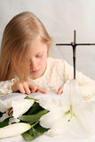 Prayer. Little girl  reading holy bible  and easter lilies lying on the table Royalty Free Stock Images