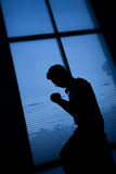 Prayer. Man kneeling and praying beside a window on an evening Royalty Free Stock Photography