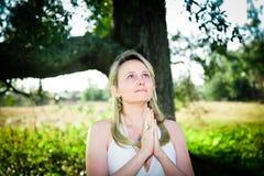 Prayer. A beautiful woman praying outside Royalty Free Stock Images