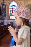 Prayer. Young adorable girl prays in a Christian church royalty free stock images