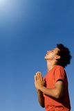 Prayer. Happy smiling young man praying, prayer stock photo