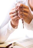 Prayer. Christian believer praying to God with rosary in hand. Vertical version Royalty Free Stock Images