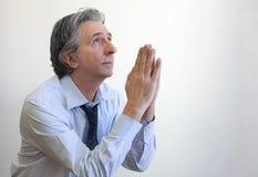 Prayer. Gray haired mature businessman praying Stock Photos