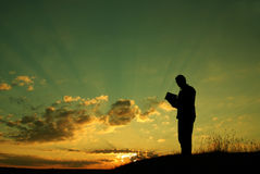 The prayer. A man holds the Holly Bible in his arms, making his morning prayer royalty free stock images