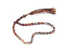 Prayer beads. Brown, black prayer beads on white background stock images
