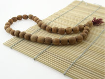 Prayer beads. Wooden prayer beads on bamboo-mat Stock Images