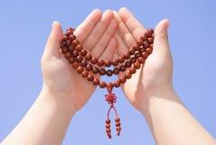 Prayer beads in her hands Stock Photos