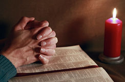 Prayer and bible with burning candle Stock Images