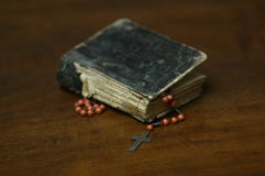 Prayer book and rosary cross. Antique crucifix rosary and book still life Stock Photography