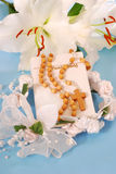 Prayer book and rosary for first holy communion. Prayer book and wooden rosary for first holy communion on blue background Royalty Free Stock Photos