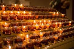 Prayer candles light up the darkness in a church Stock Photography