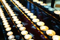 Prayer candles in rows alight glowing softly in church. Prayer candles in rows alight glowing golden and softly in church Royalty Free Stock Photos
