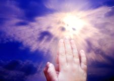 Prayer child. Child hands praying in front of a divine light coming through clouds in the sky Stock Image